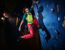 Woman practicing rock-climbing on a rock wall Stock Photo