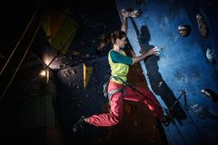 Woman practicing rock-climbing Stock Images