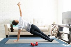 Woman practicing side plank yoga at home stock photography