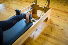Woman practicing stretching exercise on reformer stock images