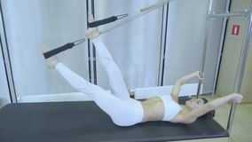 Pilates. Woman in white clothes practicing stretching exercise on reformer in gym. all series by number 01234567890001. stock video