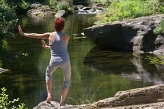 .Woman practicing Tai-Chi in front of a river. Royalty Free Stock Image