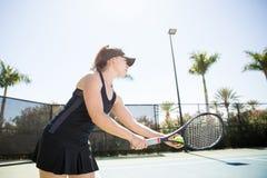 Woman practicing tennis on the court. Hispanic young woman playing tennis outdoor, practicing tennis on the tennis court on a sunny day Royalty Free Stock Photos