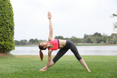 Woman practicing triangle pose outdoors on lawn,left side Stock Photo