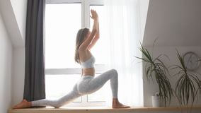 Woman practicing Warrior yoga pose indoors against window background stock video footage