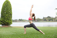 Woman practicing Warrior yoga pose outdoors on lawn,left side Royalty Free Stock Images
