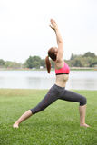 Woman practicing Warrior yoga pose outdoors on lawn,right side Stock Photos