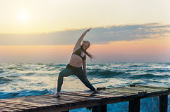 Woman practicing Warrior yoga pose outdoors over ocean or sea and sunset sky background. Royalty Free Stock Photography