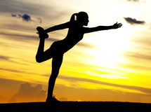 Woman practicing yoga. Silhouette of a young woman practicing yoga on the hill against yellow sky with clouds at sunset Stock Photo