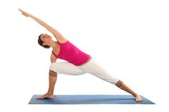 Woman practicing yoga. Woman Posing On A Blue Yoga Mat Royalty Free Stock Photography
