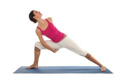 Woman practicing yoga. Woman Posing On A Blue Yoga Mat Stock Images