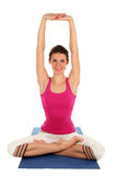 Woman practicing yoga. Woman Posing On A Blue Yoga Mat Royalty Free Stock Images