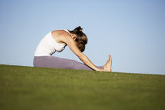 Woman practicing yoga. On a green lawn royalty free stock image
