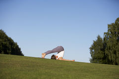 Woman practicing yoga. On a green lawn stock images
