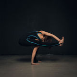 Woman practicing yoga against a dark texturized wall royalty free stock images