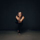 Woman practicing yoga against a dark texturized wall royalty free stock photography