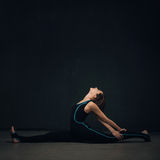 Woman practicing yoga against a dark wall royalty free stock photo