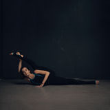 Woman practicing yoga against a dark wall stock images