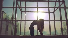 Woman practicing yoga against window background on a sunny day stock video