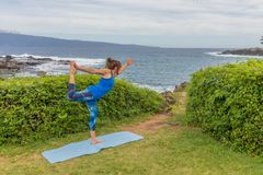 Woman Practicing Yoga on the Maui Coast. A woman practicing yoga along the scenic coast of Maui Hawaii Stock Photos