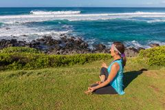 Woman Practicing Yoga Meditation on the Maui Coast. A woman practicing yoga along the scenic coast of Maui Hawaii Stock Photography