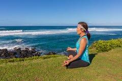 Yoga Meditation on the Maui Coast. A woman practicing yoga along the scenic coast of Maui Hawaii Stock Image