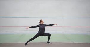 Woman practicing yoga asana warrior pose enjoying healthy lifestyle exercising outdoors stock video footage