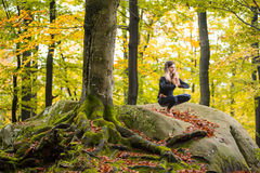 Woman is practicing yoga in autumn forest on the big stone Royalty Free Stock Photo