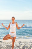 Woman practicing yoga on the beach Royalty Free Stock Photography