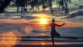 Woman practicing yoga on the beach at amazing sunset. Royalty Free Stock Images