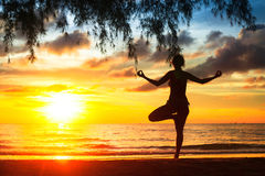 Woman practicing yoga on the beach during a beautiful sunset Royalty Free Stock Image