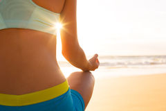Woman Practicing Yoga on the Beach at Sunset Royalty Free Stock Images