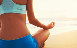 Woman Practicing Yoga on the Beach at Sunset Royalty Free Stock Photography
