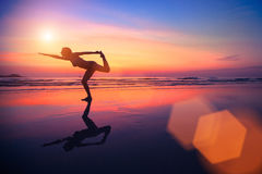 Woman practicing yoga on the beach at sunset. Royalty Free Stock Images
