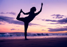 Woman practicing yoga on the beach at sunset Stock Photography