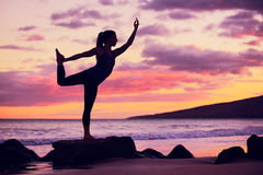 Woman practicing yoga on the beach at sunset Stock Images