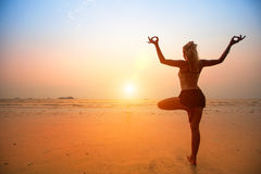 Woman practicing yoga on the beach at sunset. Royalty Free Stock Photography