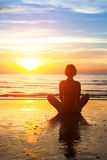 Woman practicing yoga on the beach during sunsetW Royalty Free Stock Photos