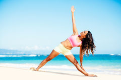 Woman practicing yoga on the beach Royalty Free Stock Image