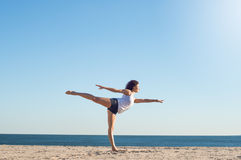 Woman practicing yoga at the beach Stock Photography