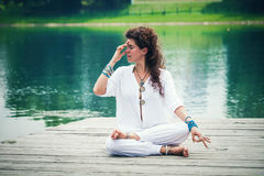 Woman practicing yoga breathing technique by the lake. Young woman wearing white comfortable clothes practicing yoga breathing technique by the lake worm summer stock photo
