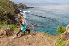 Woman Practicing Yoga on the Coast of Maui. A woman practicing yoga along the scenic coast of Maui Hawaii Royalty Free Stock Photography