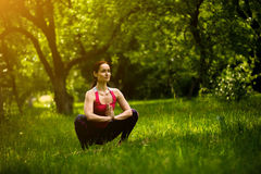 Woman practicing yoga concentrating in garland pose. In morning garden female doing Malasana. Toned image Stock Photos