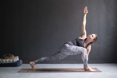 Woman practicing yoga, doing lunge exercise, Revolved Side Angle Pose. Sporty beautiful young woman practicing yoga, doing lunge exercise, Revolved Side Angle royalty free stock photos