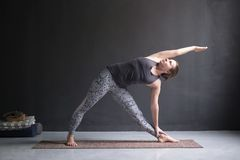 Woman practicing yoga, doing Utthita Trikonasana pose stock photos