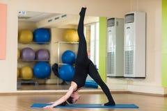 Woman practicing yoga Downward Facing Dog Stock Photography