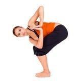 Woman Practicing Yoga Exercise. Young fit woman practicing yoga exercise called: Twisted Chair Pose sanskrit name: Parivrtta Utkatasana, isolated on white Royalty Free Stock Image
