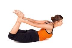 Woman Practicing Yoga Exercise Called Bow Pose. Sanskrit name: Dhanurasana, this pose improves posture, rejuvenates the spine, enhancing blood circulation Royalty Free Stock Image