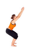 Woman Practicing Yoga Exercise Called Chair Pose. Woman practicing yoga exercise called: Chair Pose, sanskrit name: Utkatasana, this pose increases strength Stock Photo