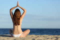 Woman practicing yoga exercises on the beach in summer Stock Images